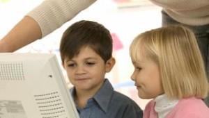 Teacher Helping Children Use Computer